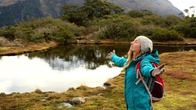 junge weibliche wandern steht bergsee und outstretches arme - rucksack stock-videos und b-roll-filmmaterial