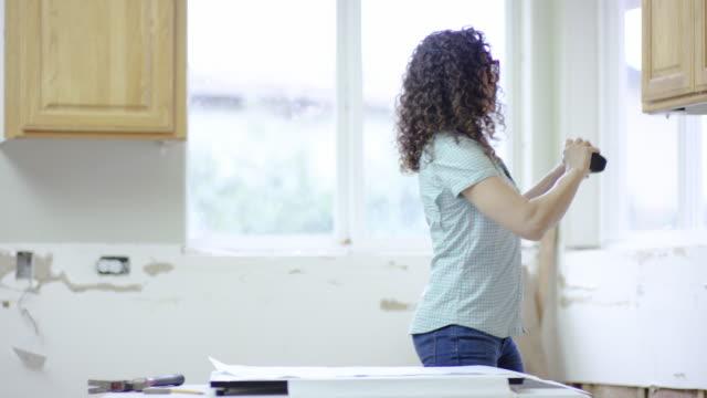 Giovane femmina proprietario di abitazione lavorando su un progetto di casa fai-da-te