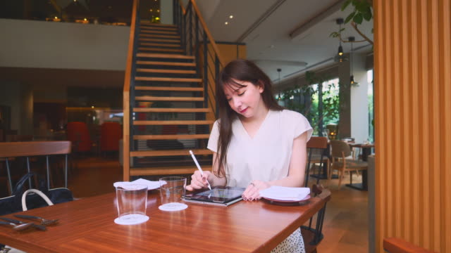 young female illustrator drawing in cozy restaurant - illustrator stock videos & royalty-free footage