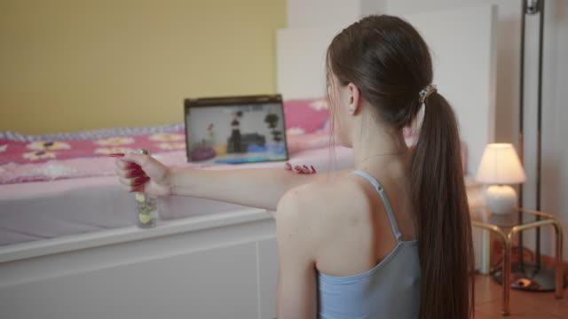 vídeos de stock e filmes b-roll de young female in quarantene doing home exercises next to tablet with video workout - exercício de relaxamento