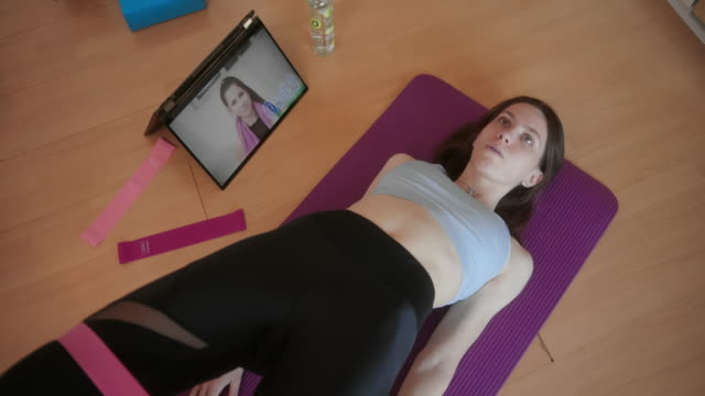 young female in quarantine doing home exercises next to tablet with video workout - fitness ball stock videos & royalty-free footage