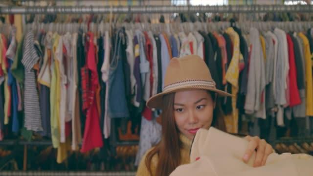 stockvideo's en b-roll-footage met jonge vrouw in vintage kleding winkel. - kledingrek