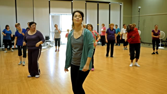 Young female instructor leads active seniors in line dancing
