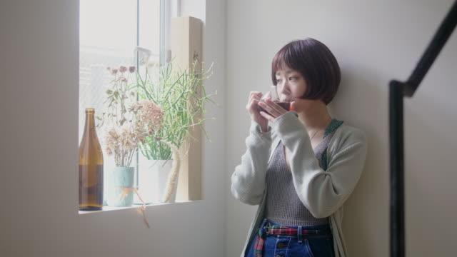 若い女性の日本人成人はコーヒーを飲んで熟考する - のみ点の映像素材/bロール