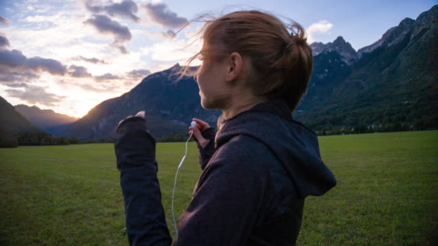 young female jogger inserting earphones in the mountainside - cuffia attrezzatura per l'informazione video stock e b–roll