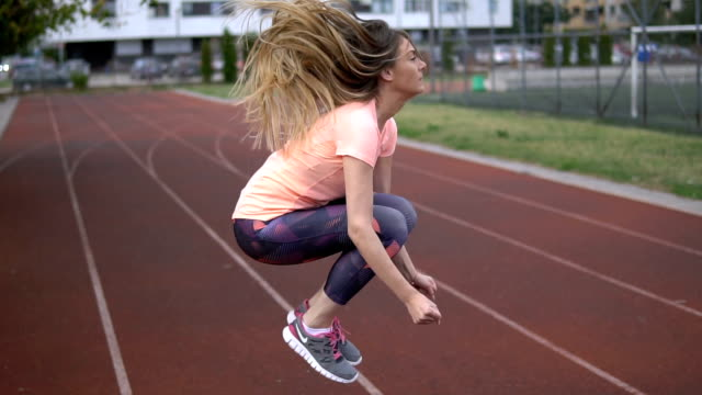 Young female jumping on sports field