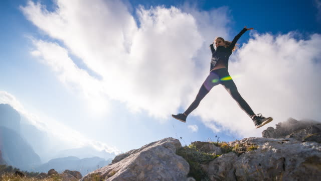 young female jumps into the sky in the mountains - arms raised stock videos & royalty-free footage