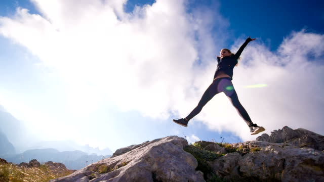 Young female jumps into the sky in the mountains