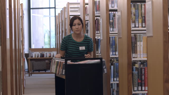 ms ts young female library employee with book cart returns books to shelves / rancho mirage, california, usa - material stock-videos und b-roll-filmmaterial