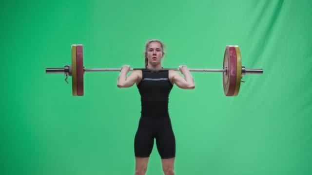 stockvideo's en b-roll-footage met jonge vrouwelijke lifter het uitvoeren van de schone en ruk lift - gewicht fysieke beschrijving