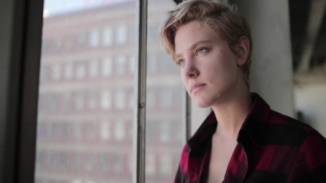vidéos et rushes de young female looking out of window in loft apartment thinking - transgenre
