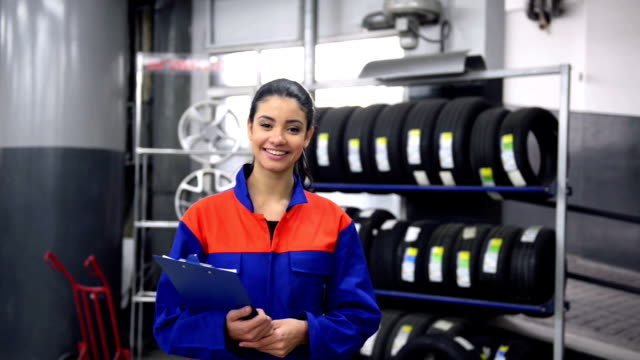 Young female mechanic posing in auto repair shop