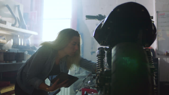 Young female mechanic swipes tablet and inspects wires on motorcycle in local auto shop.