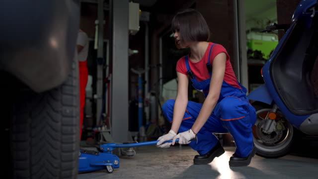 vídeos de stock e filmes b-roll de young female mechanic using a crane to lift a car for repair - pushing