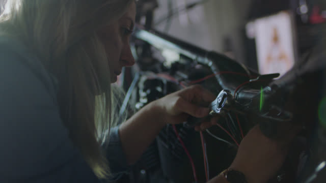vídeos de stock, filmes e b-roll de cu. young female mechanic works on motorcycle with ratcheting socket wrench in auto repair shop. - consertando