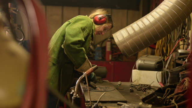 stockvideo's en b-roll-footage met young female metal artist working in old shop. - metaalindustrie