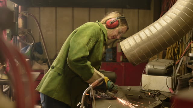 young female metal artist working in old shop. - metallic stock videos & royalty-free footage