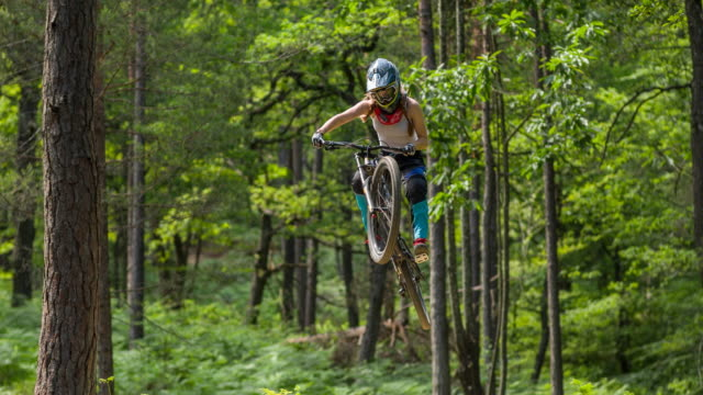 Young female mountain biker jumping towards the camera