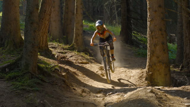 Young female mountain biker riding downhill a rocky dirt track