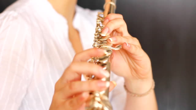 Young female musician playing flute.