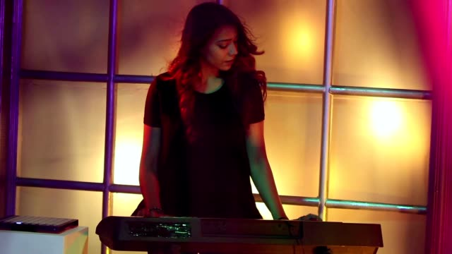 MS Young female musician singing and playing synthesizer in nightclub / India