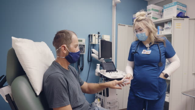 a young female nurse wearing a surgical face mask smiles as she takes the temperature of a masked male in his forties with an infrared thermometer before clipping a pulse oximeter to his index finger while having a discussion in an examination room in a m - medical examination room stock videos & royalty-free footage