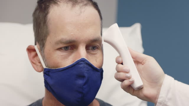 a young female nurse wearing a surgical face mask takes the temperature of a masked white male in his forties with a forehead infrared thermometer in an examination room of a medical clinic - medical examination room stock videos & royalty-free footage
