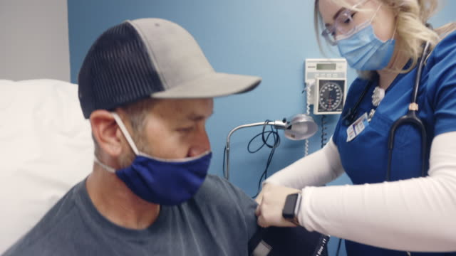 a young female nurse wearing a surgical face mask walks into an examination room of a medical clinic and places a blood pressure cuff on the arm of a masked white male in his forties - medical scrubs stock videos & royalty-free footage