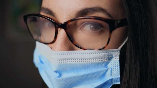 young female nurse wearing fogging up glasses because of face mask looking at you - fog stock videos & royalty-free footage