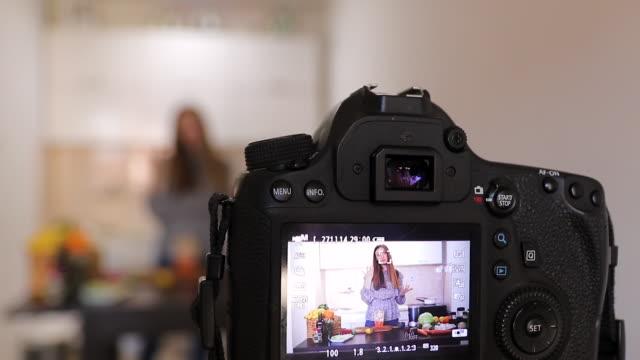 自宅でソーシャルメディアのための健康的な食べ物についてのビデオを記録する若い女性栄養士 - デジタル一眼レフカメラ点の映像素材/bロール