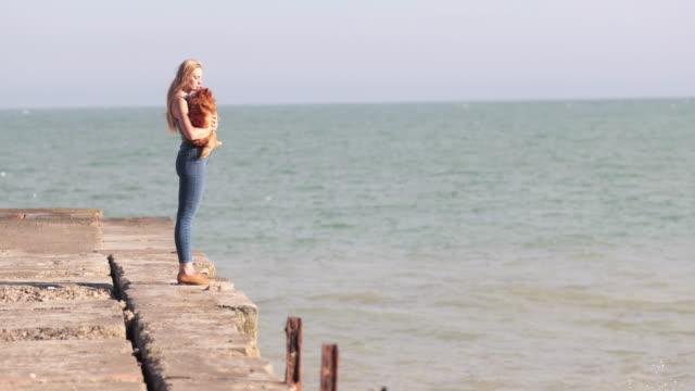 vídeos de stock, filmes e b-roll de young female on beach with pet dog - sem manga