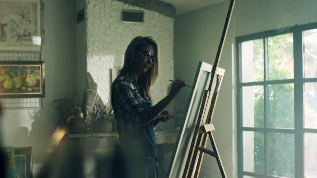 Joven mujer pintora en el taller del artista