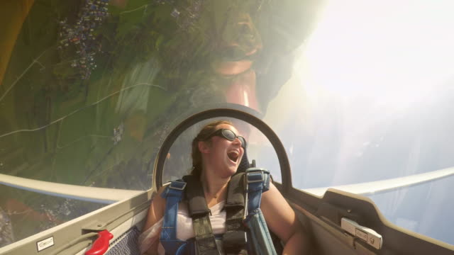 ld young female passenger in the glider having a great time as the pilots turns the glider upside down a few times - glider stock videos & royalty-free footage