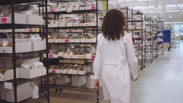 4K UHD: Young female pharmacist walking past aisles of medications