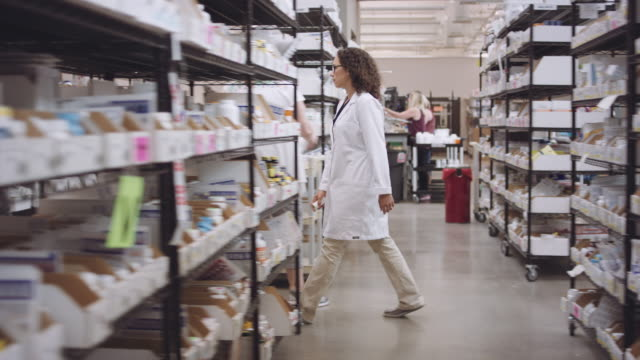 4K UHD: Young female pharmacist walking through aisles of medications