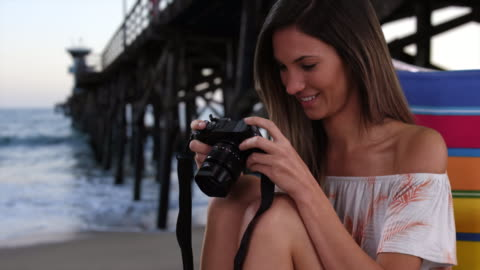 young female photographer in her 20s sitting in chair at beach next to pier - digital spegelreflexkamera bildbanksvideor och videomaterial från bakom kulisserna