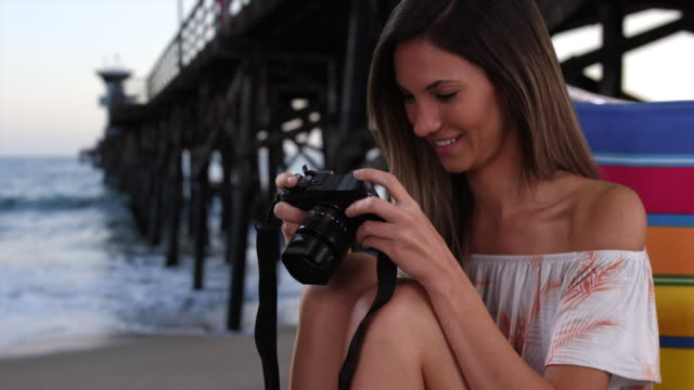 Young female photographer in her 20s sitting in chair at beach next to pier