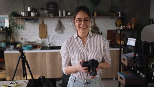 彼女のホームオフィスのキッチンのセットアップでポーズをとる若い女性写真家 - デジタル一眼レフカメラ点の映像素材/bロール