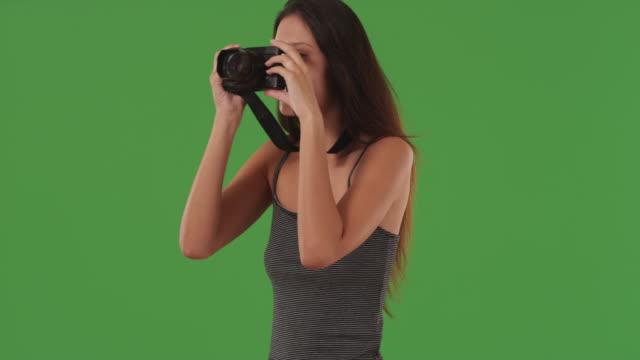 Young female photographer taking pictures with digital camera on greenscreen