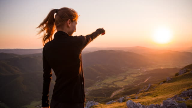 Young female pointing at beautiful view of sunset in mountainside