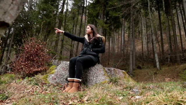 Young female pointing with hand in forest
