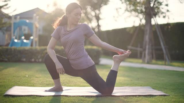 vidéos et rushes de jeune femelle pratiquant le yoga dans le stationnement public - assis en tailleur