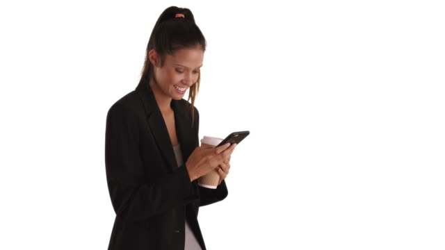 Young female professional  text messaging on cell phone with white background