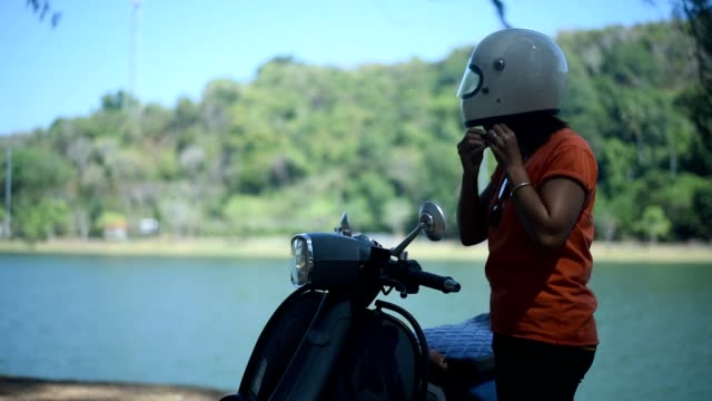 young female putting on helmet near her scooter, beside the lake. - crash helmet stock videos and b-roll footage