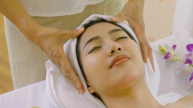 young female receiving a facial massage - facial massage stock videos and b-roll footage