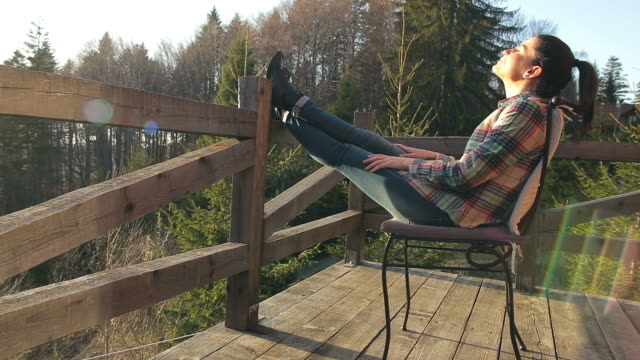 young female relaxing on the cabin balcony. - log cabin stock videos & royalty-free footage