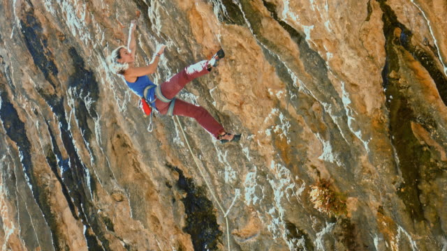 young female rock climber scaling in the pyrenees - climbing stock videos & royalty-free footage