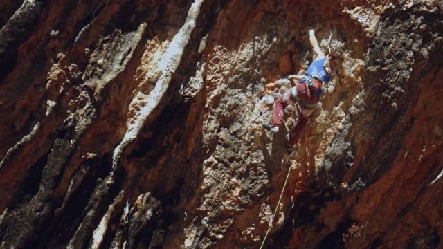 Young female rock climber scaling inside a cave in the Pyrenees