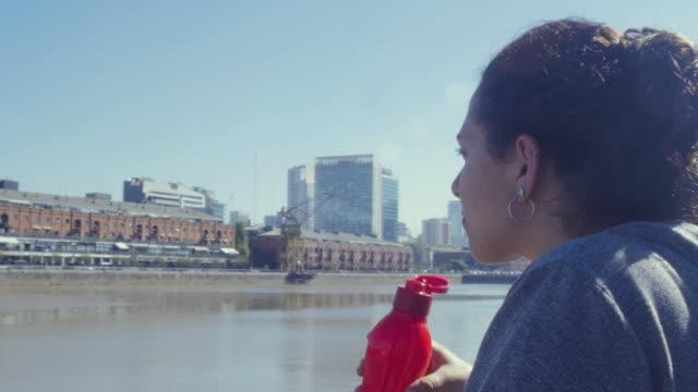 ウォーターフロントパークで水を飲みながら川を渡って建物を見ている若い女性ローラースケーター - プエルトマデロ点の映像素材/bロール