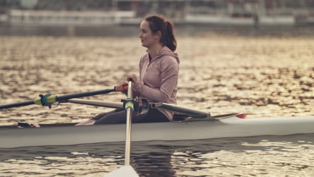 young female rowing boat in city during sunset - skill stock videos & royalty-free footage